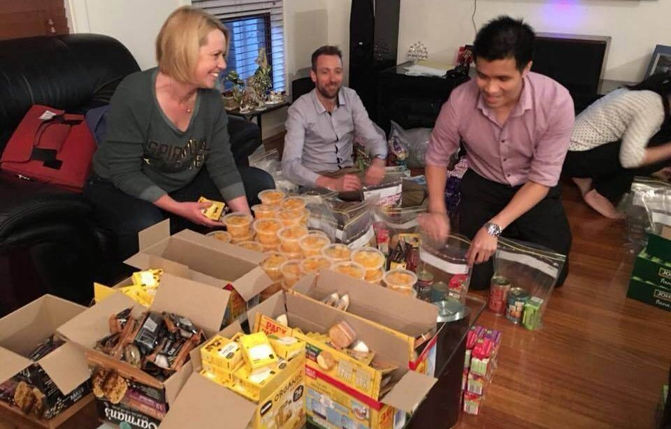 A group of people packing Care Packs in a lounge room