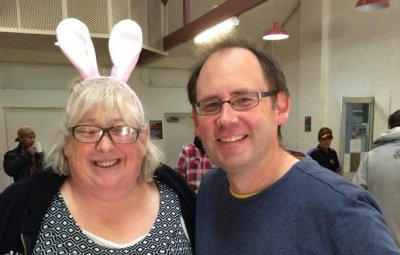 A lady in bunny ears, and a man standing in a room