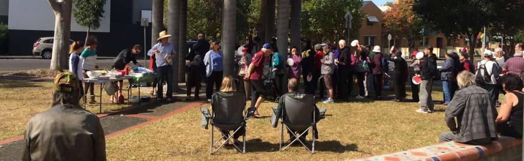 A group of people waiting for food in a park