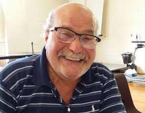 A smiling middle aged man with a moustache