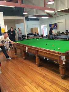 Men playing pool in a hall