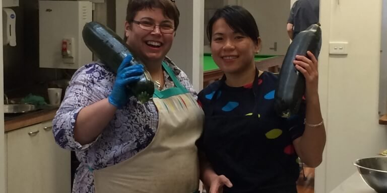 2 ladies holding giant zucchinis in a kitchen